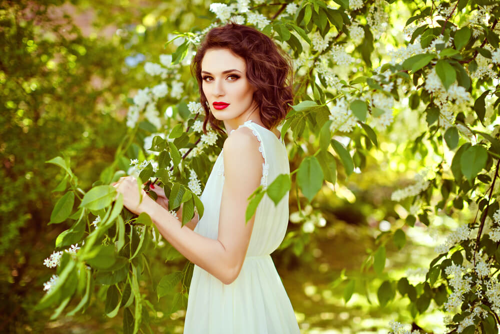 Beautiful young woman in white dress in the garden