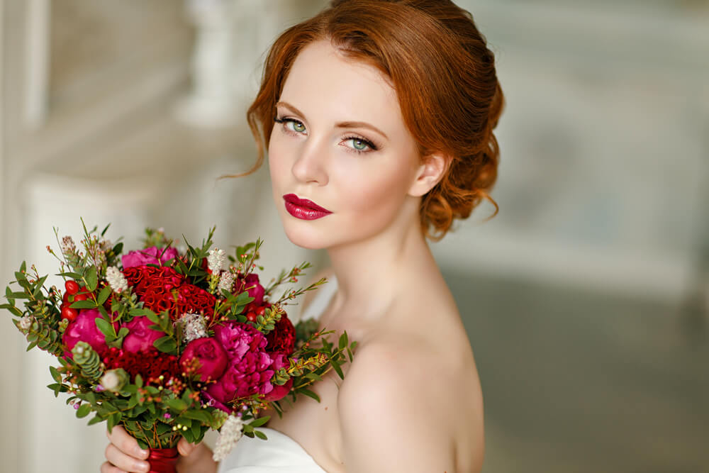 Beautiful red-headed bride with bouquet of red roses